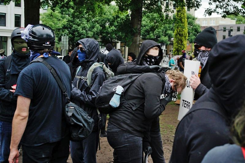 PMG PHOTO: KIT MACAVOY - An anti-fascist counter-protester helps a colleague secure a black bandana.