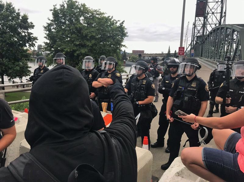 PMG PHOTO: ZANE SPARLING - Portland Police keep anti-fascist protesters on one side of the Willamette while the far-right protesters have marched to the other side. As of noon, the protest had seen much national attention and a lot of shouting but little violence.