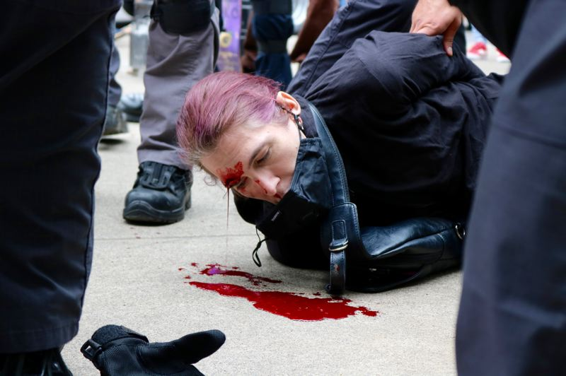 PMG PHOTO: ZANE SPARLING - A black-clad protester bled onto the sidewalk near the Morrison Bridge during a protest on Saturday, Aug. 17 in Portland.