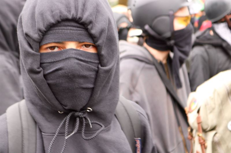 PMG PHOTO: ZANE SPARLING - A person wears the trademark mask and black clothing associated with the anti-fascist fighters known as Antifa during a protest on Saturday, Aug. 17 in Portland.