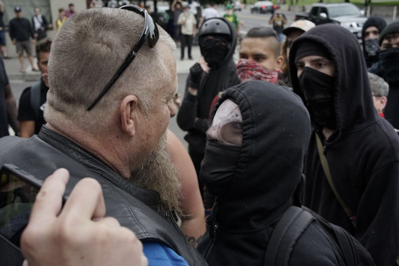 PMG PHOTO: KIT MACAVOY - A black-clad member of antifa stands off with a protester in downtown Portland on Saturday, Aug. 17.