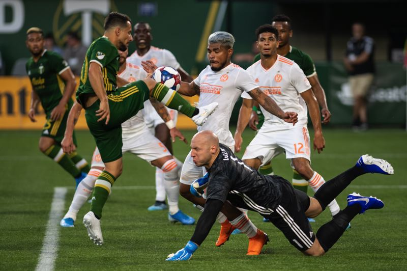 PMG PHOTO: CHRISTOPHER OERTELL - Portland Timbers midfielder runs into an assortment of Atlanta United players, including goalkeeper Brad Guzan, during Sunday night's 2-0 home loss at Providence Park.
