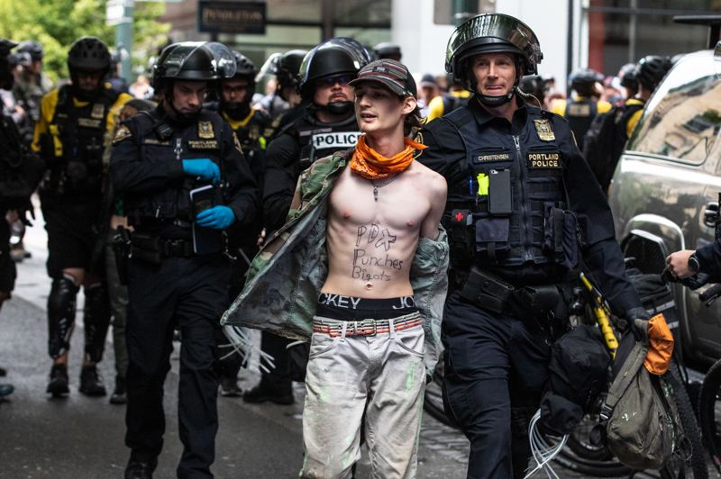 PMG PHOTO: JON HOUSE - A man with the words 'PDX punches bigots' written on his chest is arrested after a skirmish with Portland Police during a downtown protest on Saturday.