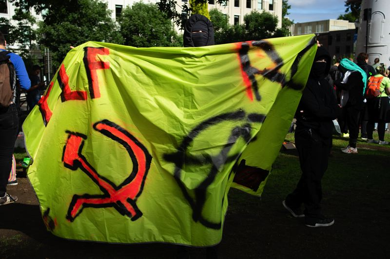 PMG PHOTO: KIT MACAVOY - Antifa members carry a sign with the Soviet Union symbol for communism and an anarchy emblem at a waterfront rally in Portland on Saturday, Aug. 17.