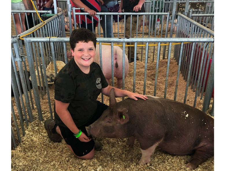 PMG PHOTO: NOAH WASS - Tyler Kruse of Newberg with his sleepy pig, Hank, a six-month-old 250-pound Duroc pig.