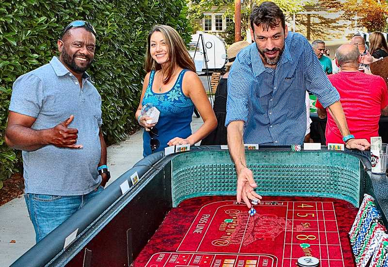 DAVID F. ASHTON - Whilst playing casino games at the benefit Eastmoreland Block Party, guests Craig Dwyer and Christie Echeverri watch - as Joseph Echeverri tries to roll lucky 7s.