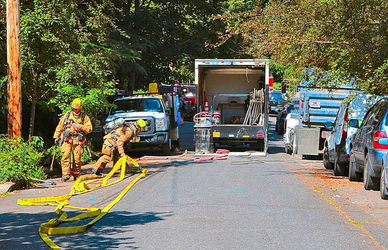 DAVID F. ASHTON - PF&R firefighters laid out protection water lines, should the gas escaping from the pavement ignite - while NW Natural Gas workers were getting busy with the repair of the ruptured pipe.