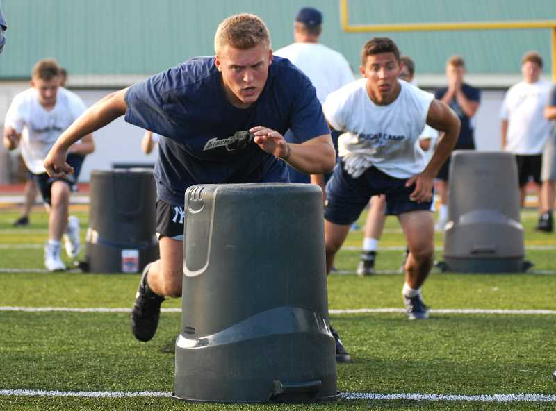 PMG PHOTO: DEREK WILEY -  Bryant Raeburn practices a defensive drill during Canby High School's football camp.