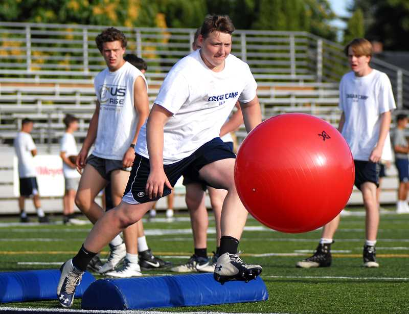 PMG PHOTO: DEREK WILEY - Nick Vandecoevering tackles a ball during a defensive drill at Canby High School.