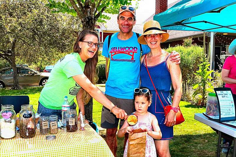 DAVID F. ASHTON - Set up in front of SMILE Station during Summerville, Moreland Farmers Market Board Member Kristen Eberlin served up custom-blended granola for Olivia French, while mom and dad Bert and Lisa look on.