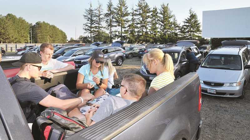 GRAPHIC PHOTO: GARY ALLEN - Drive-in attendees often arrive early to get a good spot, then wile away the hours playing games, eating dinner or chatting with neighbors.