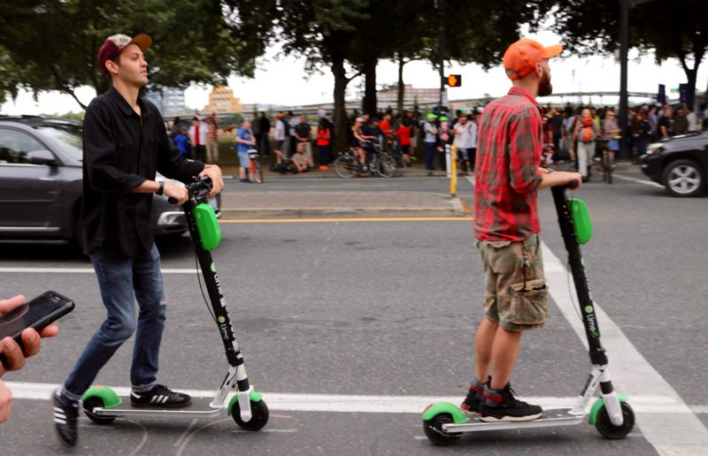 PMG PHOTO: ZANE SPARLING - Two electric scooter riders zip down Southwest Naito Parkway in Portland on Saturday, Aug. 17.
