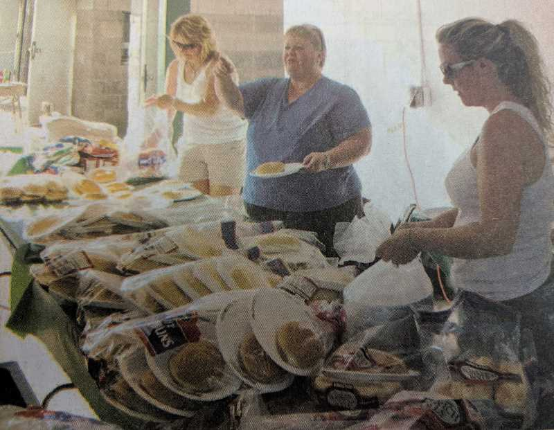 ARCHIVE PHOTO - Estacada High School Booster Club volunteers Darcy Nenow, Pam Gould and Josette Swan prepare food during the first home football game of the school year in 2009. The group had recently raised funds for a covered area at Ranger Stadium.
