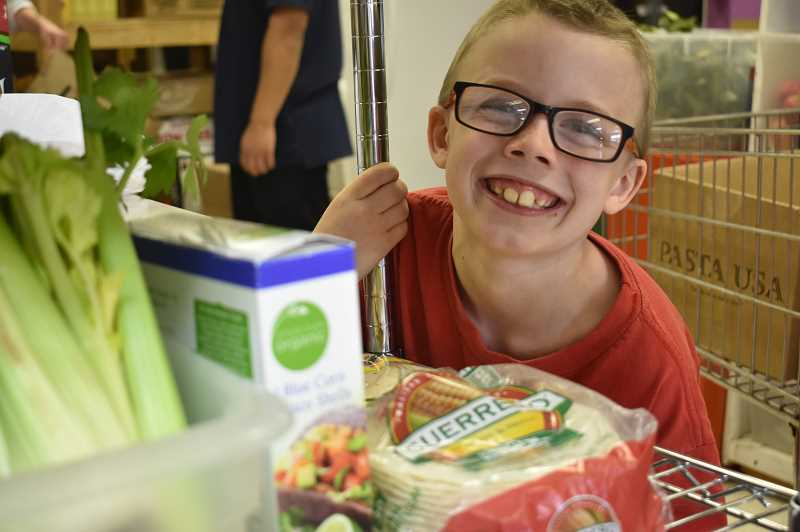 PMG PHOTO: EMILY LINDSTRAND - Xander Bevercombe, 9, is all smiles while working at the Estacada Area Food Bank.