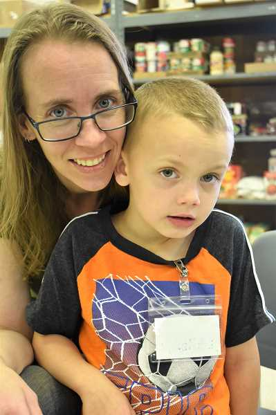 PMG PHOTO: EMILY LINDSTRAND - Natasha Bevercombe and her son Landon, 6, are frequent volunteers at the Estacada Area Food Bank.