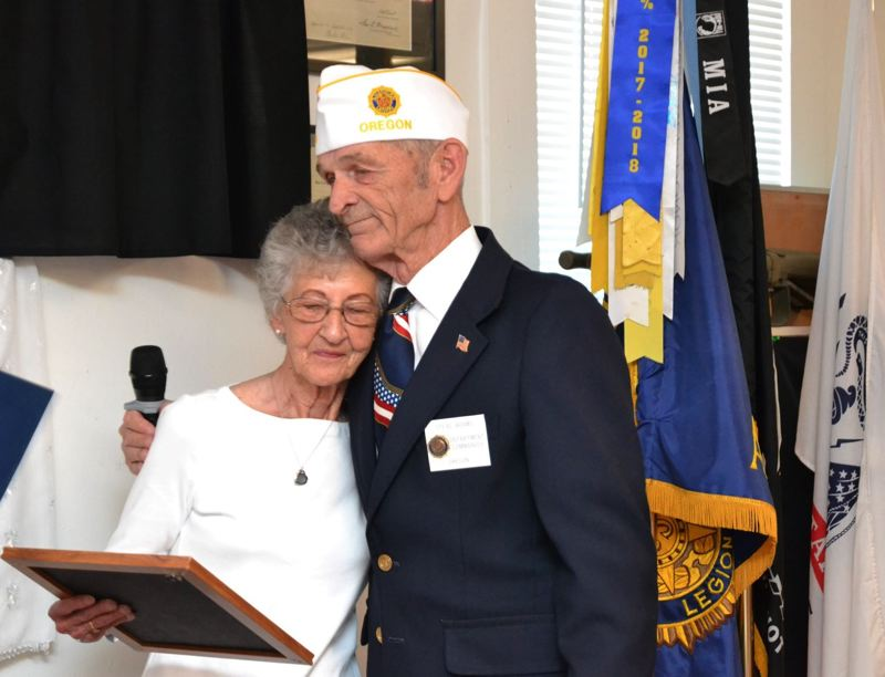 COURTESY PHOTO - American Legion Department Commander Steve Adams embraces Ellen Kalmbach after giving her a framed photograph of her late husband, John Kalmbach.