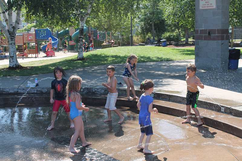 PMG PHOTO: HOLLY BARTHOLOMEW - Fountains like the one at at Tanner Creek provide kids a fun opportunity to stay cool on hot summer days.