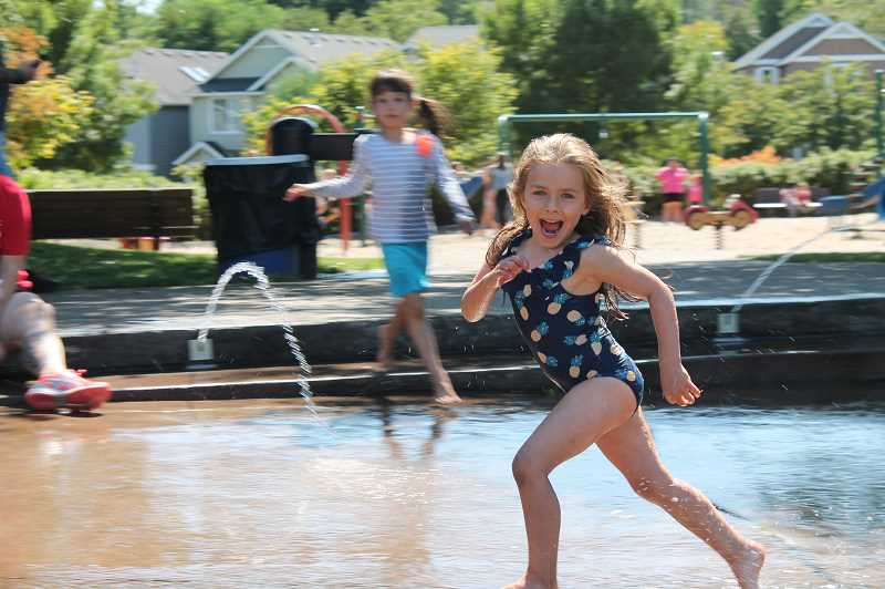 PMG PHOTO: HOLLY BARTHOLOMEW - Summer camper Everett runs through the Tanner Creek fountain.
