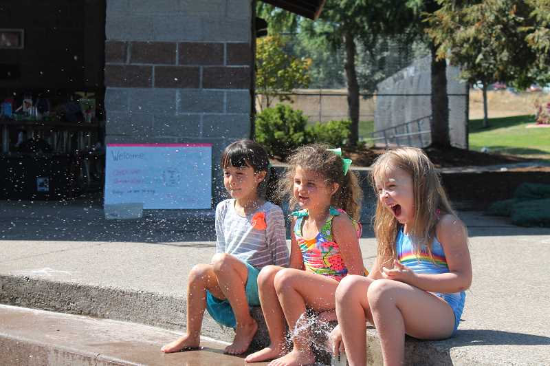 PMG PHOTO: HOLLY BARTHOLOMEW - Campers sit just on the edge of the fountain, though not far enough away to avoid the splashes.