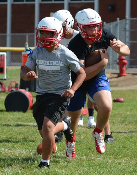 PMG PHOTO: DAVID BALL - Centennial players go through a running play during a morning session.