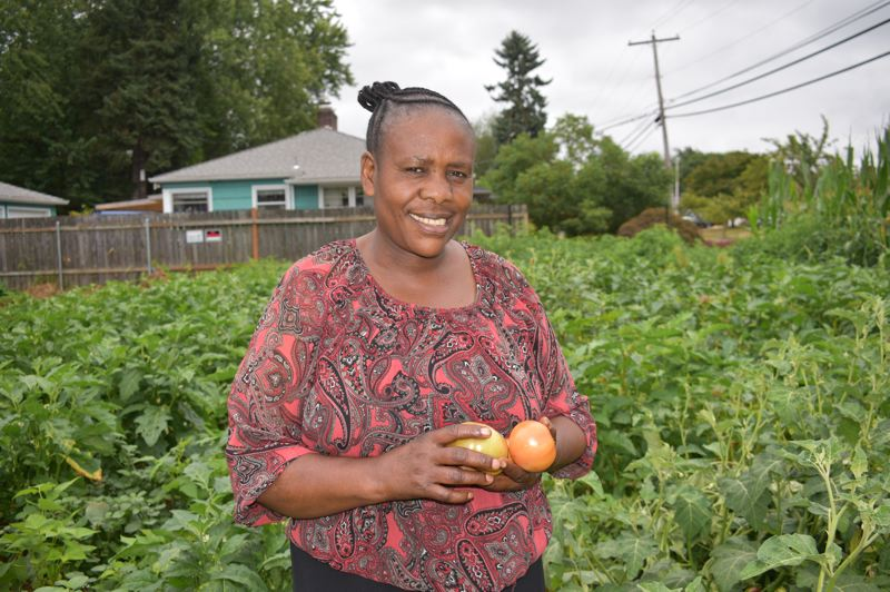 PMG PHOTO: TERESA CARSON - Zawadi Baderha, from the Democratic Republic of Congo and one of the gardeners at the community garden at Adventist Health Portland, shows off some of her produce.