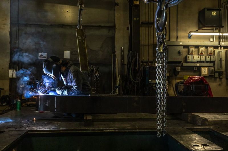 TRIBUNE PHOTO: JONATHAN HOUSE  - Carissa Carambot welds the bottom fork of a log stacker at Sherwood-based Allied Systems.