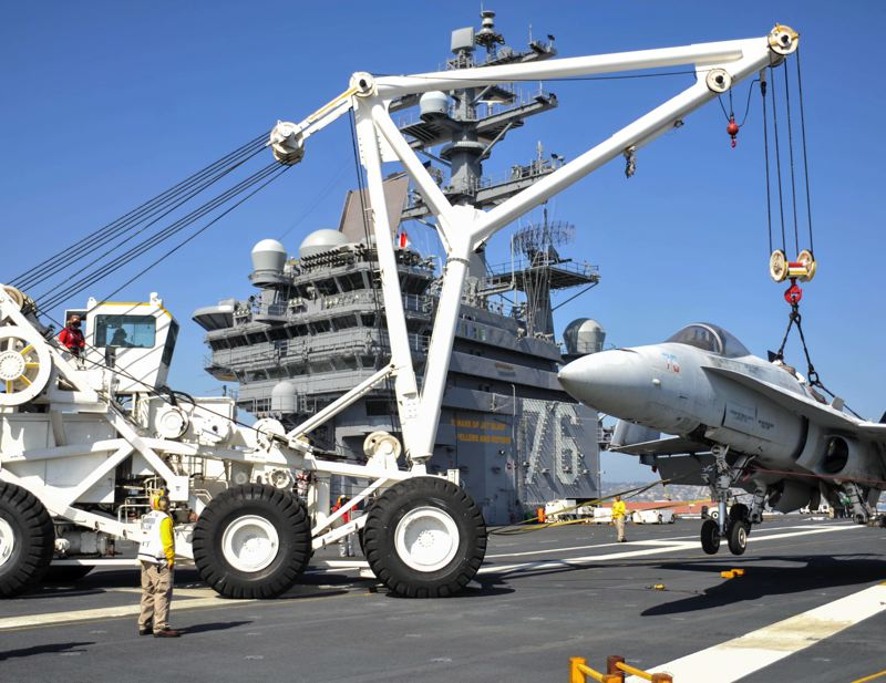 PHOTO COURTESY: U.S. NAVY, MASS COMMUNICATION SPECIALIST 3RD CLASS JONATHAN NELSON - U.S. Navy sailors use a crash and salvage crane to lift a non-functional McDonnell Douglas F/A-18 Hornet during flight deck drills aboard the aircraft carrier USS Ronald Reagan (CVN-76). Sherwood-based Allied Systems Co. in June was awarded a $70 million, five-year grant to provide as many as 37 new crash cranes for the U.S. Navy. The next generation of cranes will replace a model of cranes similar to the one pictured that are currently used to move damaged aircraft on the decks of carrier ships.
