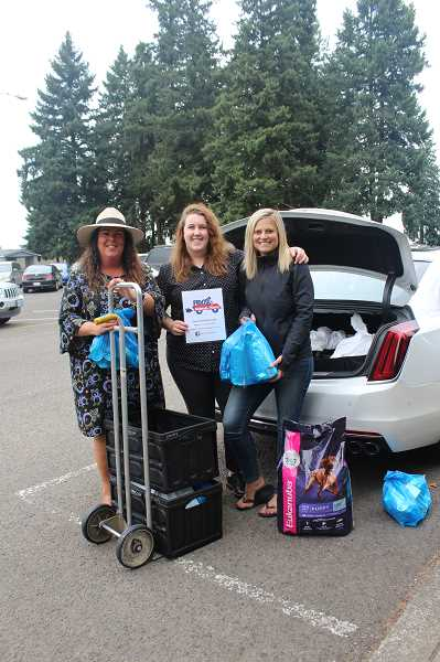 PMG PHOTO: KRISTEN WOHLERS - From left, Donna Ellison, Hannah Ellison and Stefanie Tewalt of Ellison Team Homes deliver pet food and litter to the Canby Adult Center on Wednesday, Aug. 21.