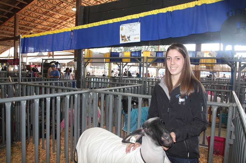 PMG PHOTO: JUSTIN MUCH - Katie Hanson of Gervais poseswith Miss Daisyat theOregon State Fair Friday, Aug. 23, 2019.Hanson has been showing animals at the state fair since she was 3 years old.
