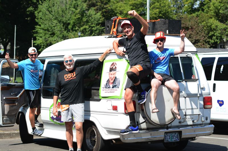 PMG PHOTO: DAVID BALL - Members of the Hoodzilla team pose on their van, with speakers blaring from the roof rack, during a layover at Main City Park on Friday afternoon.