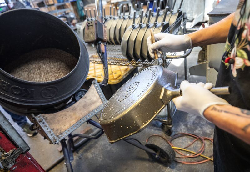 TRIBUNE PHOTO: JONATHAN HOUSE - Joshua Christler coats a Finex cast iron pan with oily flax seed before it is baked and finished at the companys Northwest Portland production facility.