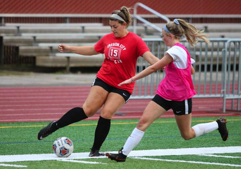 PMG PHOTO: JIM BESEDA - Oregon City senior forward Abi Willet (left) tries to evade senior defender Maddy Phelps during Thursdays varsity scrimmage at Pioneer Memorial Stadium. The Pioneers season opener is Sept. 9 at Southridge.