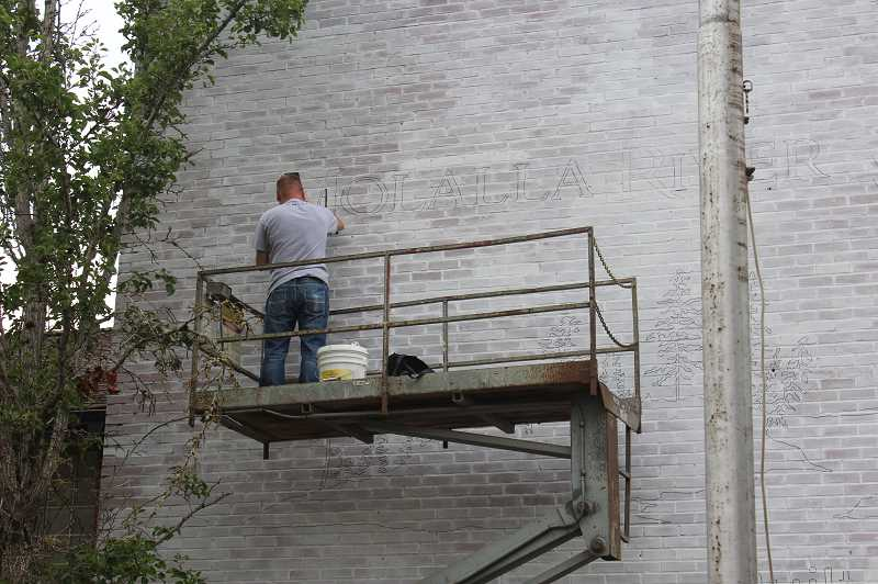 PMG PHOTO: KRISTEN WOHLERS - With white-washing finished, Jake Taylor begins painting the words 'Molalla River Middle School' on the building.