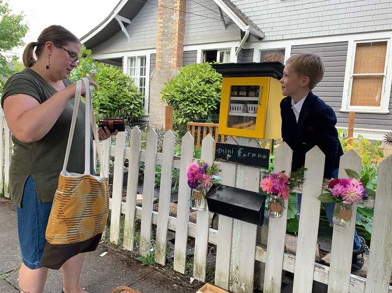 PMG PHOTO: GEOFF PURSINGER - Megan Mathis buys honey from her neighbor, 8-year-old Byrum Brooks. Brooks summer job has been selling vegetables, honey and other items.