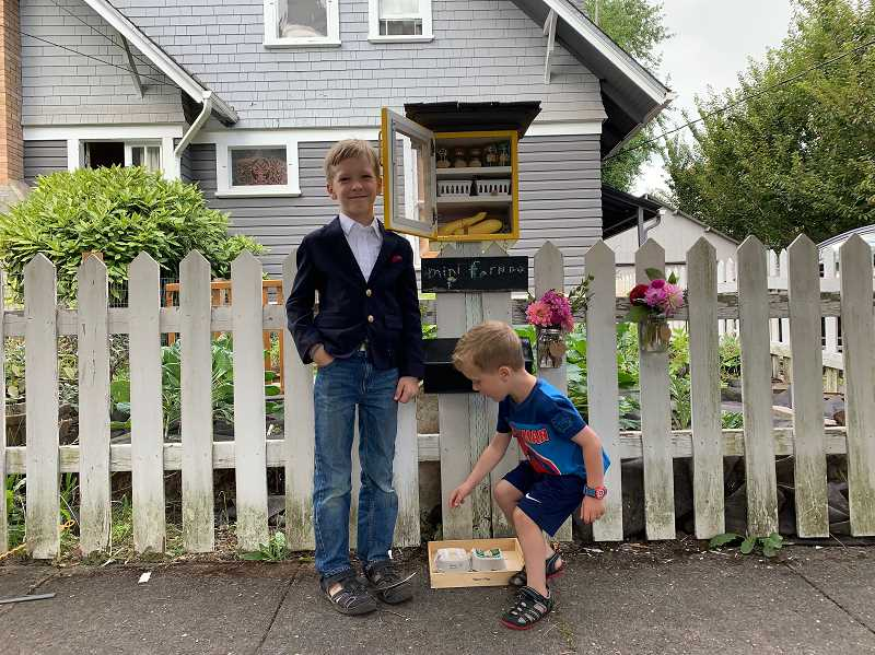 PMG PHOTO: GEOFF PURSINGER - Byrum Brooks, 8, runs the Mini Farm Box from his yard with his younger brother, Shep, 4.