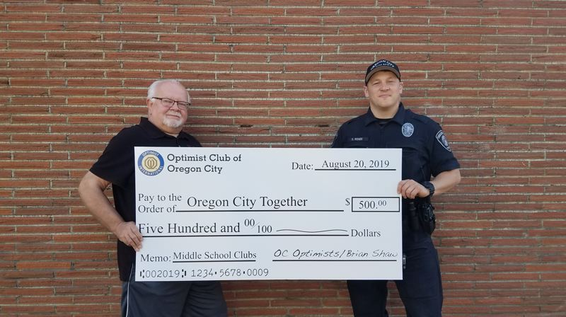 COURTESY PHOTO - Oregon City Together board member Brian Shaw presents $500 generated from his recent birthday celebration to Oregon City Police Officer Spencer Rohde.