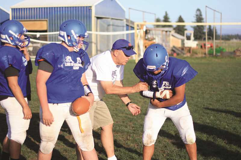 PMG PHOTO: PHIL HAWKINS - Head coach Tracy Jackson helps teach how to fake — and sell — a handoff and what it will do to defenses looking for the ball.