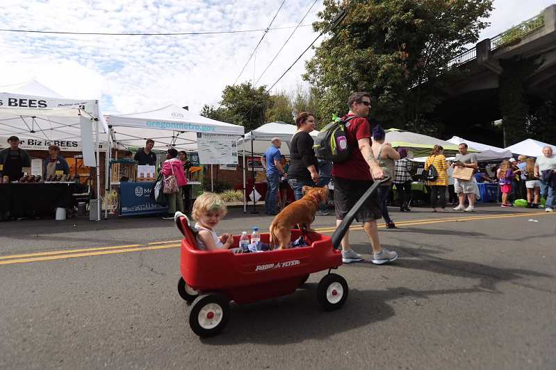 TIMES PHOTO: JAIME VALDEZ - A youngster enjoys a wagon ride down  Tigards Main Street during the 7th Annual Explore Downtown Tigard Street Fair and Latino Festival. , Times - News The annual event included music, food and almost 200 vendors lining Downtown Tigard Tigard Street Fair and Latino Festival draws hundreds to Main Street