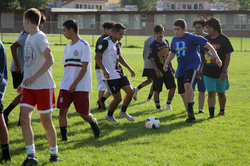 STEELE HAUGEN - Junior Leo Gutierrez, center, helps the new White Buffalo boys soccer team with footwork drills. Gutierrez scored 10 goals and assisted on three, earning honorable mention Tri-Valley honors last season.