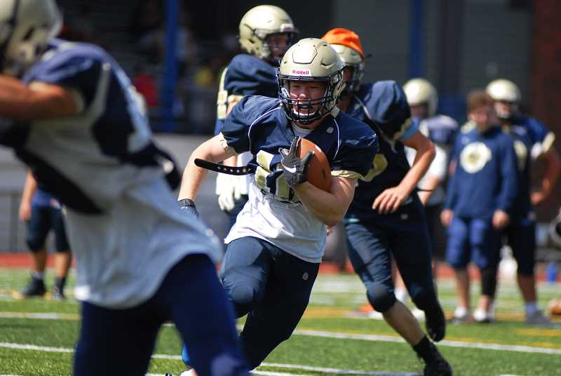 PMG PHOTO: DEREK WILEY - K'den McMullin carries the ball during football practice at Canby High School last week.