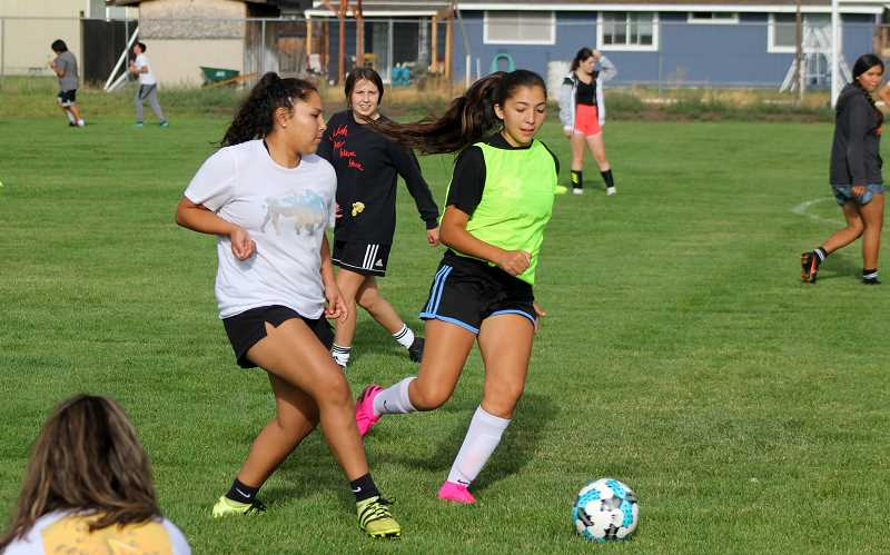 STEELE HAUGEN - Seniors Jiana Smith-Francis and Kelsey Olivera, left, hustle during a passing drill at practice. 