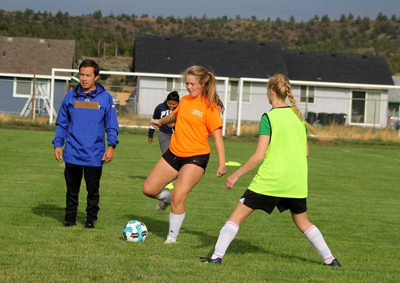STEELE HAUGEN - Junior Hannah Holiday kicks the ball during drills as head Madras coach Shawn Darrow intructs the players.