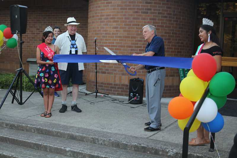 PMG PHOTO: JUSTIN MUCH - Mayor Eric Swenson does the honors at city hall. The 2019 Fiesta Mexicana court was onhand to help celebrate during the Woodburn City Council meeting/gala, which included ribbon cuttings at four completed projects: city hall renovation, peace pole and Library Park play equipment.