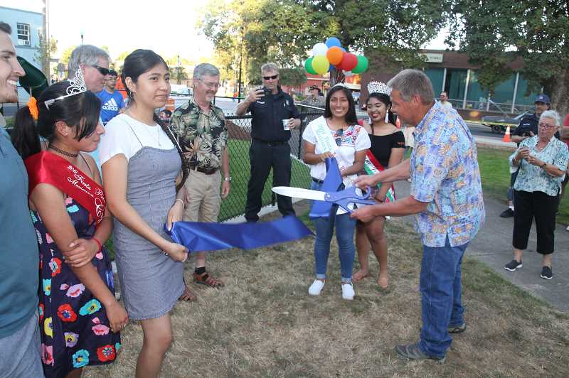 PMG PHOTO: JUSTIN MUCH - Rotary President Paul Iverson does the honors. The 2019 Fiesta Mexicana court was onhand to help celebrate during the Woodburn City Council meeting/gala, which included ribbon cuttings at four completed projects: city hall renovation, peace pole and Library Park play equipment.