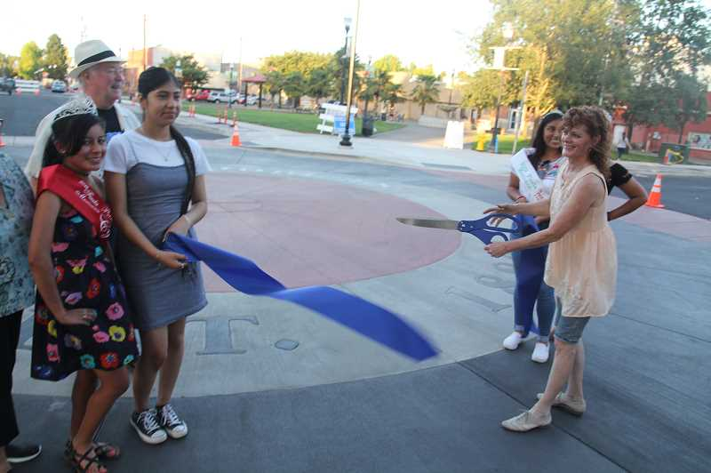 PMG PHOTO: JUSTIN MUCH - Councilor Marybeth Cornwell does the honors. The 2019 Fiesta Mexicana court was onhand to help celebrate during the Woodburn City Council meeting/gala, which included ribbon cuttings at four completed projects: city hall renovation, peace pole and Library Park play equipment.
