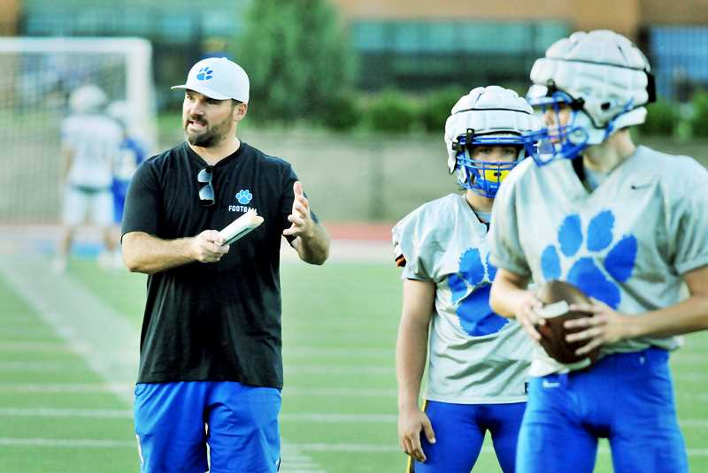 GRAPHIC PHOTO: GARY ALLEN - NHS coach Kevin Hastin runs his players through drills in anticipation of the Tigers' Sept. 6 game versus South Salem.
