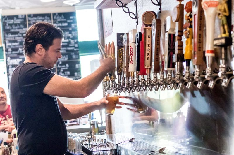 PMG PHOTO: JONATHAN HOUSE - Austin Gibbons pours a beer at FlyBoy Brewery in Tigard.