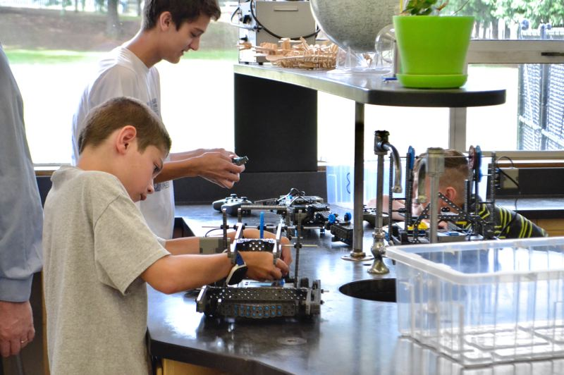 PMG PHOTO: BRITTANY ALLEN - Several high schoolers helped younger students build and code their robots at robotics camp last week.