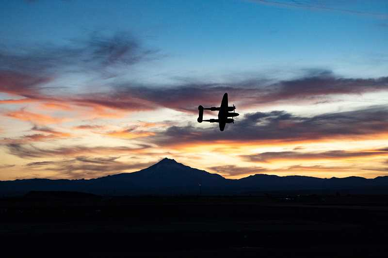 PHOTO BY JASON BLACKMAN - A P-38 Lightning, from Erickson Aircraft Collection, makes a low pass at sunset Friday night at the Airshow of the Cascades.