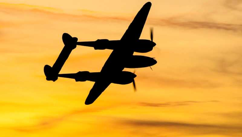 PHOTO BY TOM BROWN - A P-38 Lightning, from the Erickson Aircraft Collection, is silhouetted in the sunset on the opening night of the Airshow of the Cascades, Aug. 23.